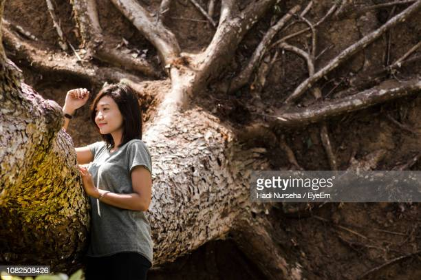 Smiling Young Woman Touching While Standing By Fallen Tree