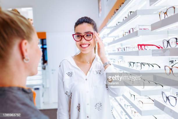 jovem sorridente experimentando óculos vermelhos na loja - spectacles - fotografias e filmes do acervo