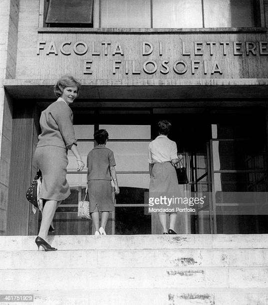 Smiling young woman turning back while climbing the stairs toward the entrance of the humanities faculty. Italy, 1950s