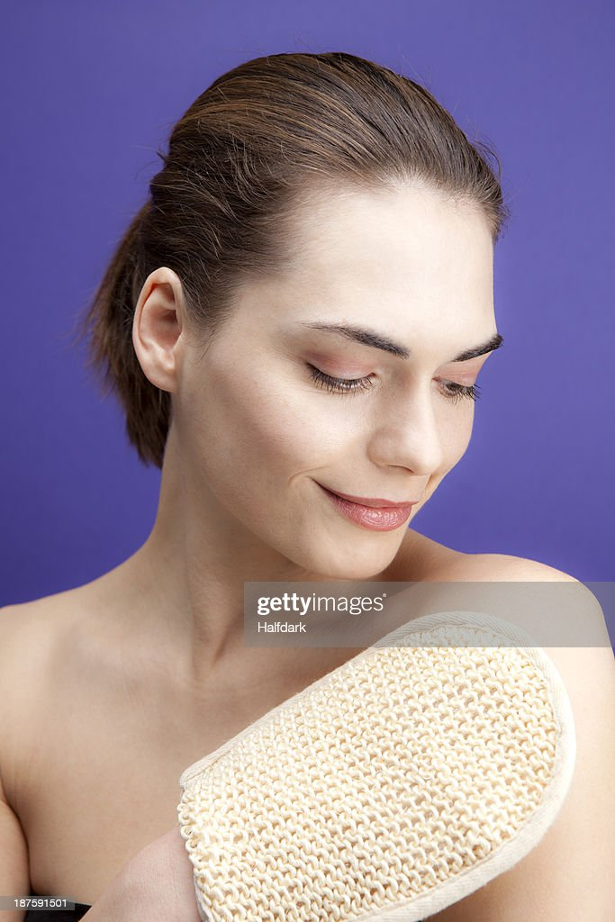 A smiling young woman using a loofah sponge : Foto de stock
