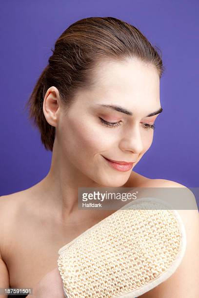 a smiling young woman using a loofah sponge - loofah stock photos and pictures