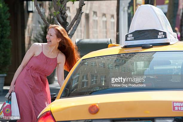 Smiling Young Woman using a Taxi