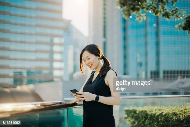 Smiling young woman using cell phone in city, with modern corporate buildings behind as background