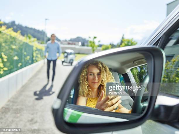 smiling young woman using cell phone in electric car - umweltfahrzeug stock-fotos und bilder
