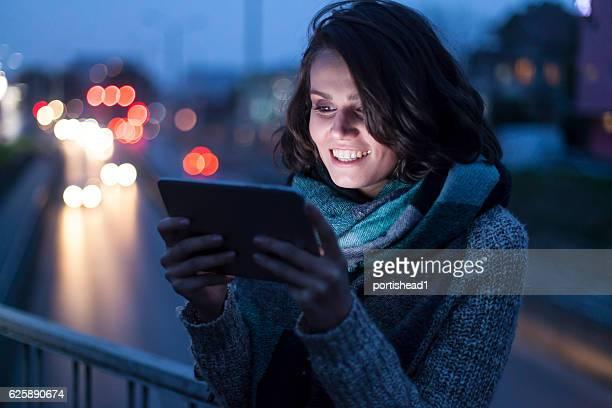 Lächelnde Junge Frau mit Digitaltablett auf Brücke bei Nacht