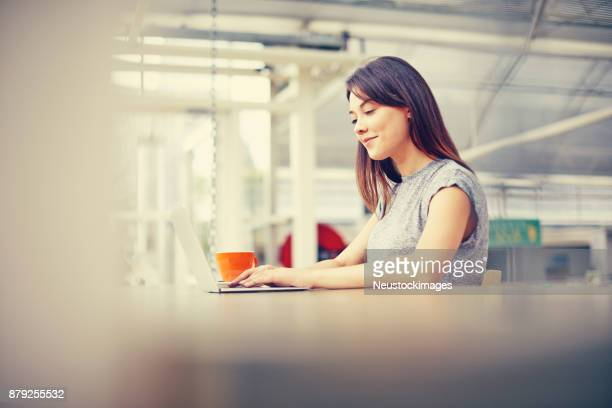Smiling young woman using laptop at cafe table