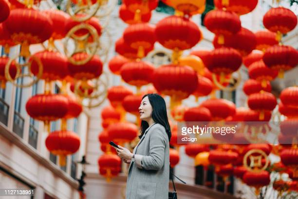 smiling young woman using mobile phone in the city, with traditional chinese red lanterns on the background - chinese lantern festival stock pictures, royalty-free photos & images