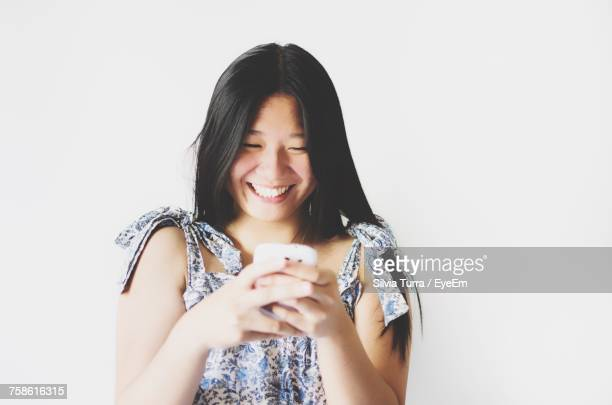 Smiling Young Woman Using Mobile Phone While Standing Against White Background