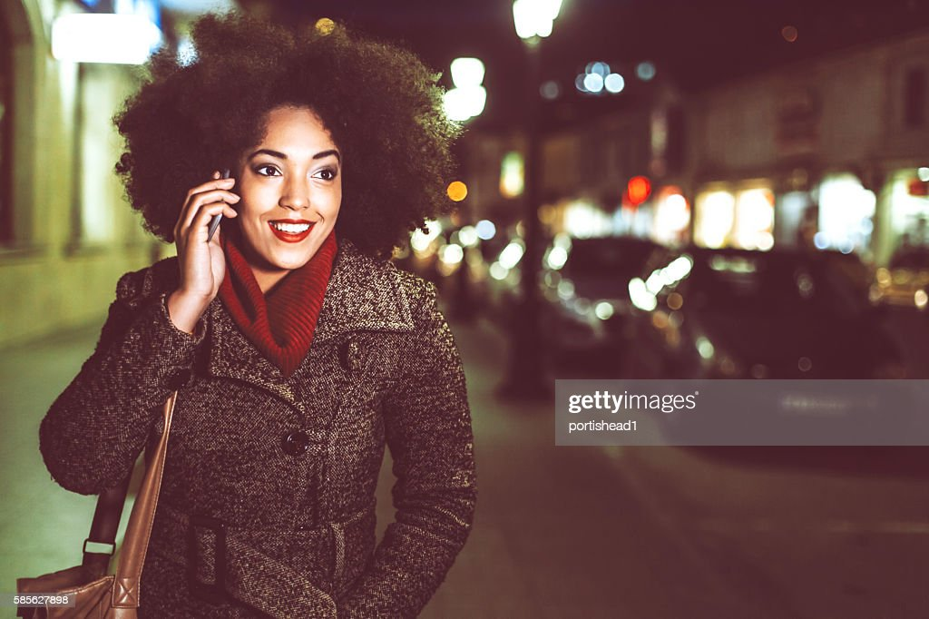 Smiling young woman using phone on street by night : Stock Photo