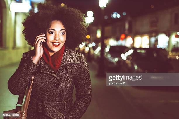 Smiling young woman using phone on street by night