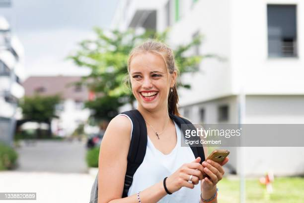 smiling young woman using phone - sigrid gombert stock pictures, royalty-free photos & images
