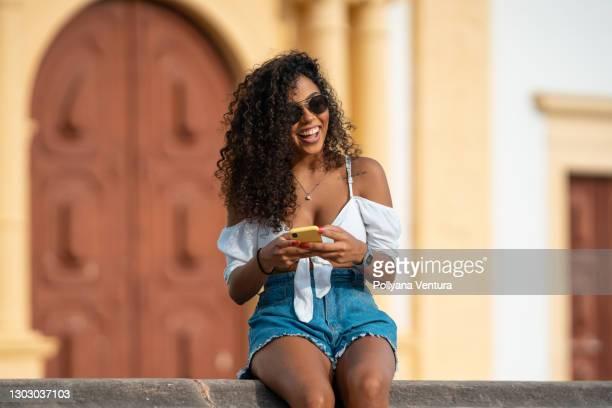 smiling young woman using smart phone - sentar se imagens e fotografias de stock