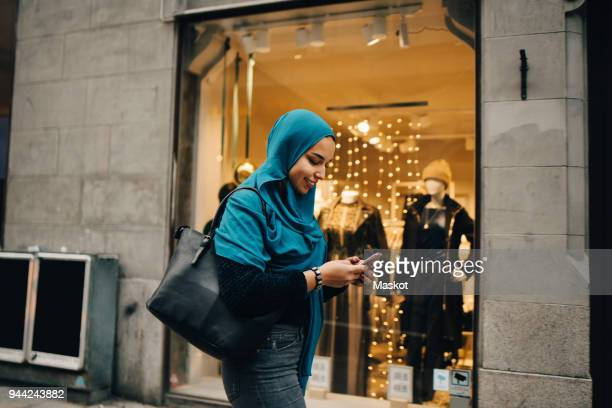 Smiling young woman using smart phone walking by store window in city