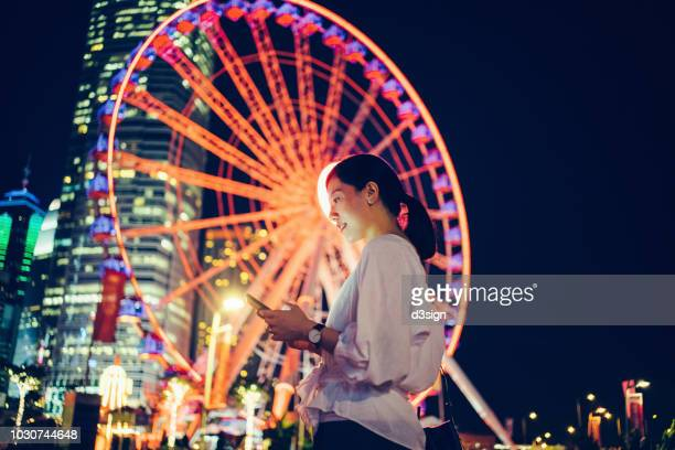 smiling young woman using smartphone in city, against illuminated ferris wheel and city skyline at night - bright colour stock pictures, royalty-free photos & images