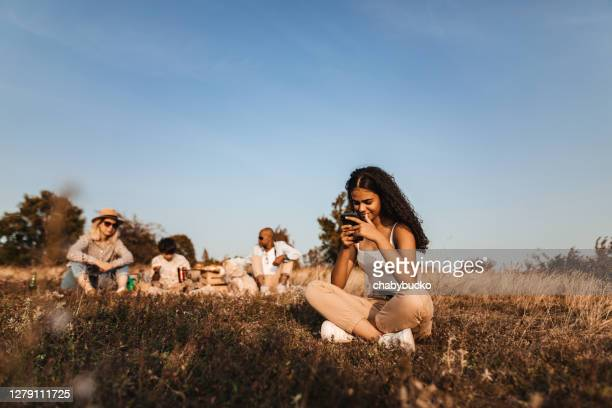 smiling young woman using smartphone while her family enjoys picnic time - four people stock pictures, royalty-free photos & images