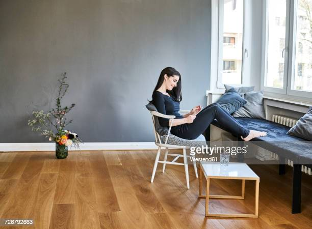 Smiling young woman using tablet at home