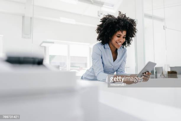smiling young woman using tablet in office - convenience stock photos and pictures