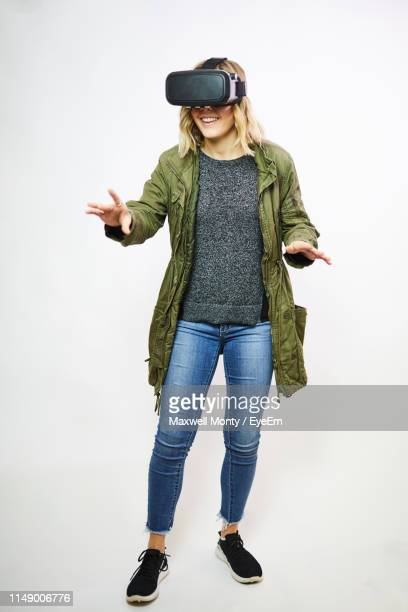smiling young woman using virtual reality against white background - simulatore di realtà virtuale foto e immagini stock