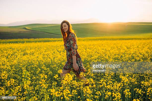 smiling young woman walking in a rape field at twilight - macedonia country stock pictures, royalty-free photos & images