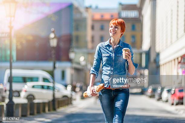 smiling young woman walking in the city with coffee and baguette - baguette photos et images de collection