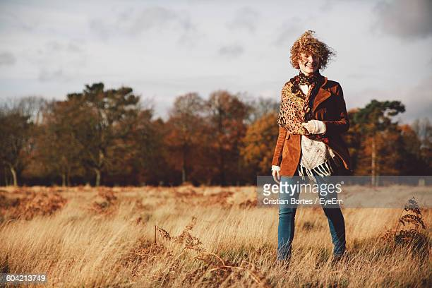 smiling young woman walking on agricultural field against sky - bortes stockfoto's en -beelden