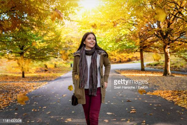 smiling young woman walking on road amidst trees in park - walking stock pictures, royalty-free photos & images