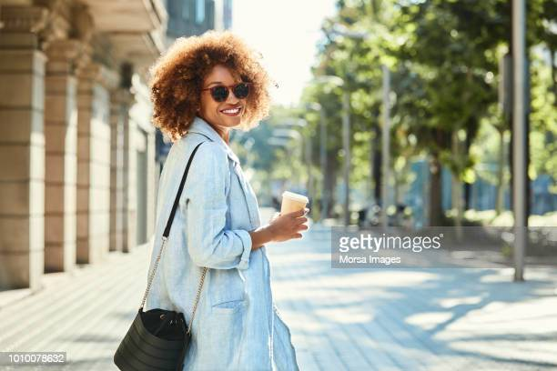 smiling young woman walking on sidewalk in city - black purse stock pictures, royalty-free photos & images