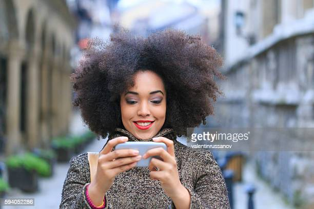 Smiling young woman walking on street and making selfie