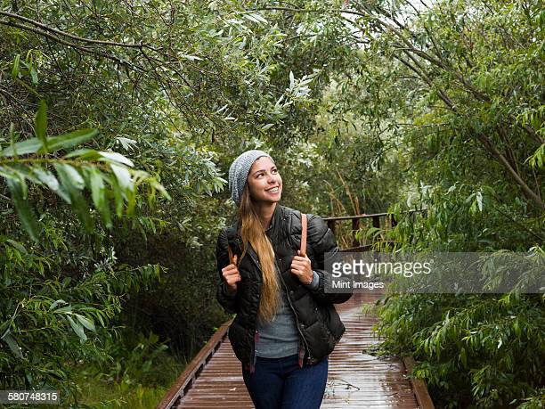 Smiling young woman walking through woodland in a park.