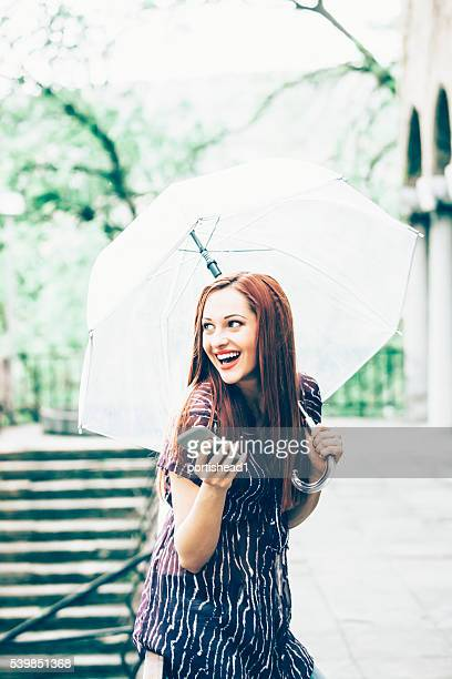 Smiling young woman walking with umbrella under the rain