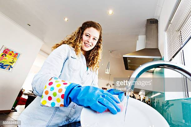 Smiling young woman wastefully washing dishes under running water