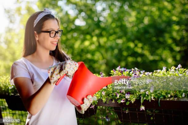 Sourire de fleurs d'arrosage jeune femme sur le balcon