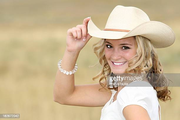 smiling young woman wearing a cowboy hat - cowboy hat stock photos and pictures