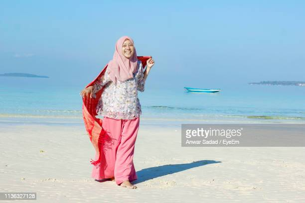 Smiling Young Woman Wearing Hijab Walking At Beach Against Clear Blue Sky During Sunny Day
