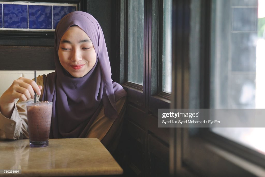 Smiling Young Woman Wearing Hijab While Having Drink At Restaurant : Stock Photo