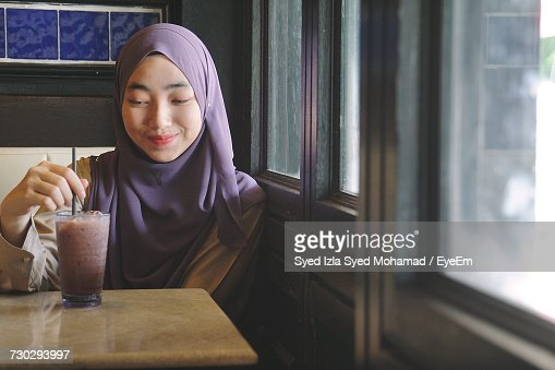 Smiling Young Woman Wearing Hijab While Having Drink At Restaurant