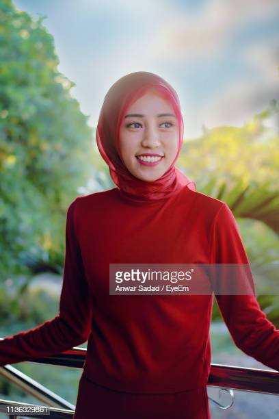 Smiling Young Woman Wearing Hijab While Looking Away Outdoors