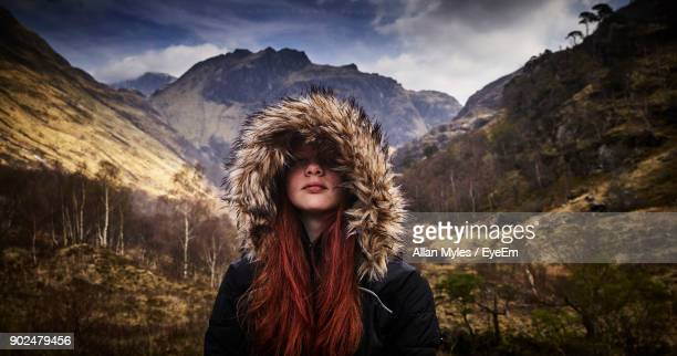 smiling young woman wearing hooded jacket against snow covered mountains - fur jacket stock pictures, royalty-free photos & images