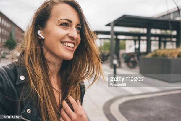 smiling young woman wearing in-ear phones - tecnologia mobile foto e immagini stock