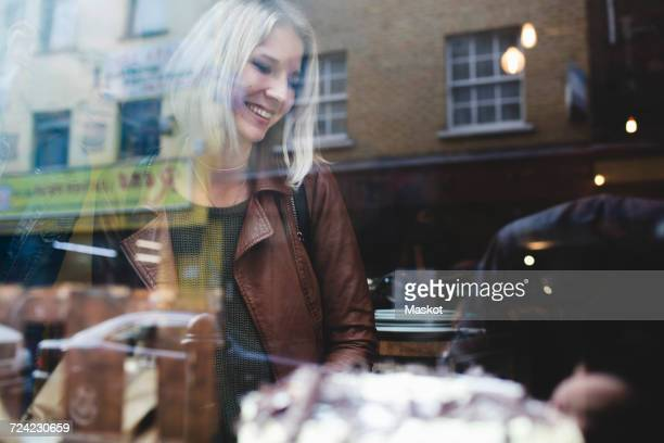 smiling young woman wearing jacket in coffee shop seen through window - shoreditch stock photos and pictures