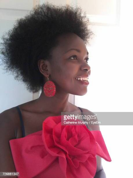 Smiling Young Woman Wearing Pink Dress Standing Against White Wall