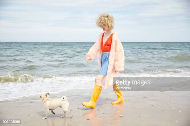 Smiling young woman wearing rain coat and Wellington boots going walkies with her dog at seaside