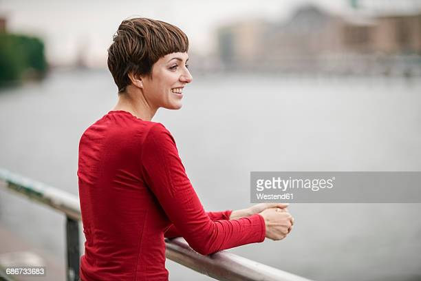 smiling young woman wearing red shirt looking at distance - sleeve stock photos and pictures