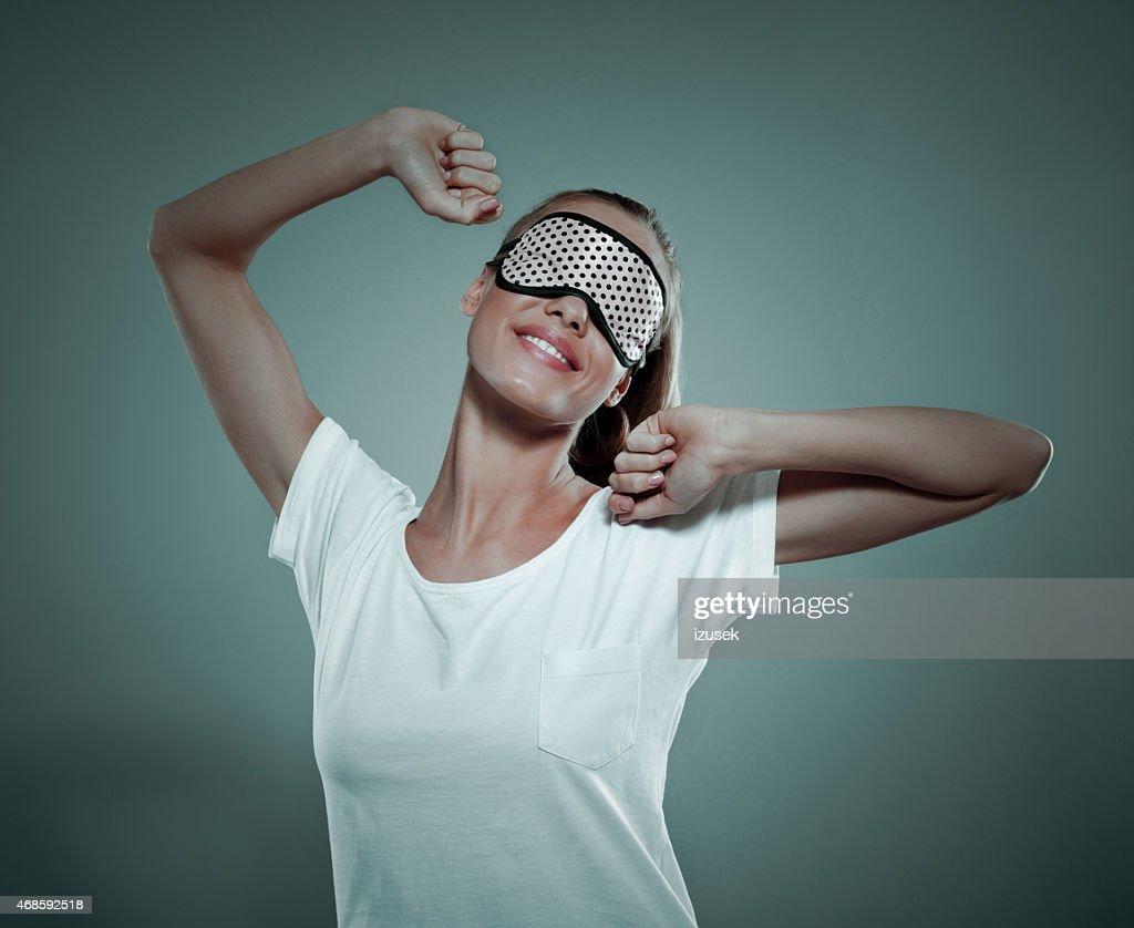 Sorridente giovane donna con dormire Maschera per gli occhi : Foto stock