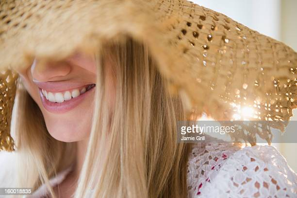 smiling young woman wearing straw hat - strohoed stockfoto's en -beelden