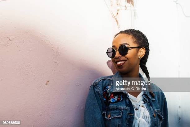 smiling young woman wearing sunglasses and denim jacket standing by white wall - braided hair stock pictures, royalty-free photos & images