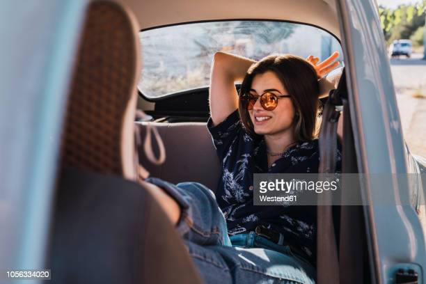 smiling young woman wearing sunglasses sitting in a car - distante fotografías e imágenes de stock
