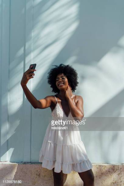 smiling young woman wearing white dress taking a selfie at a wall - サンドレス ストックフォトと画像