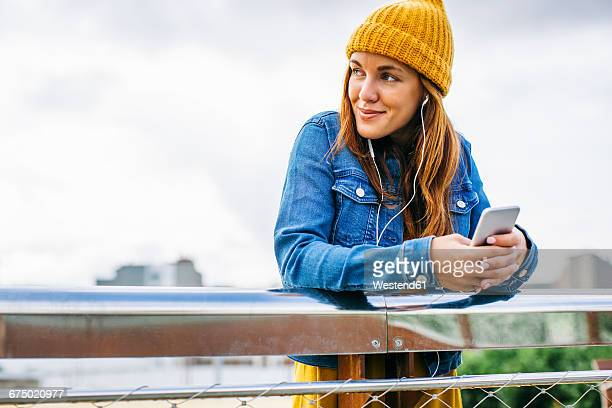 Smiling young woman wearing yellow cap listening music with earphones