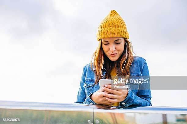 smiling young woman wearing yellow cap looking at cell phone - yellow hat stock pictures, royalty-free photos & images